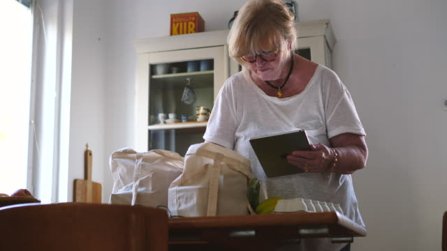 Senior woman cross-checking groceries in bag while holding digital tablet at dining table