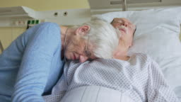 Senior woman crying next to her sick husband in hospital bed