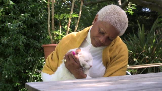 Senior Woman Cuddling Cat in Garden