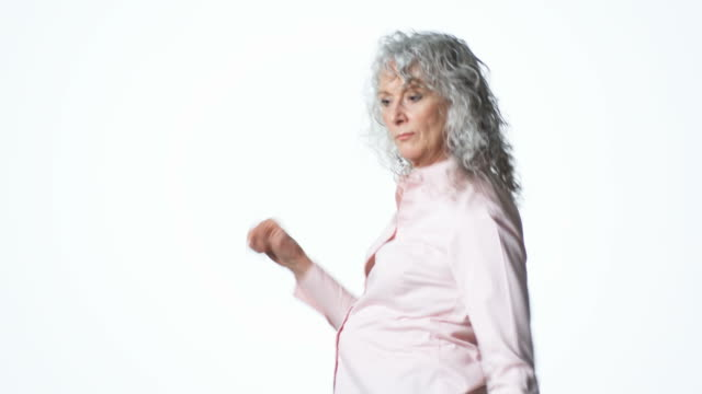 senior woman dancing against a white background