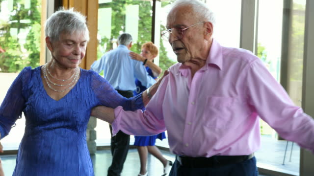 TS ZI Senior woman dancing with partner in community center