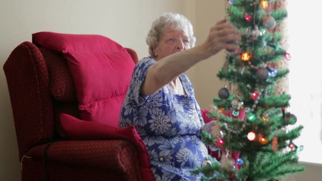 senior woman decorating a christmas tree - real people stock videos & royalty-free footage