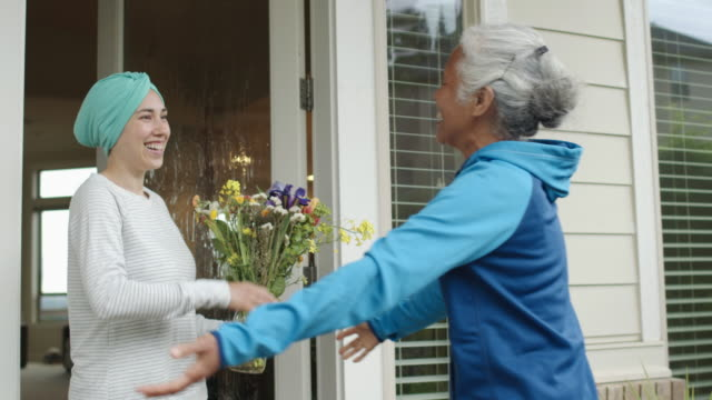 senior woman delivering flowers to a friend with cancer - chronic illness stock videos & royalty-free footage