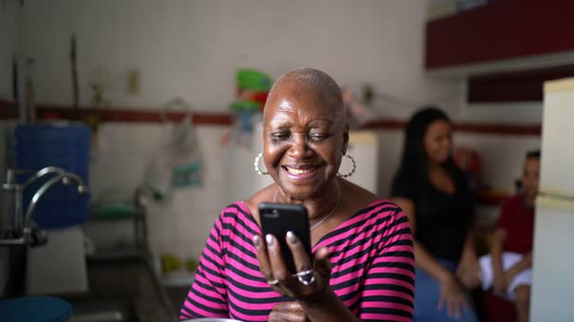 vídeos de stock, filmes e b-roll de idosa fazendo uma chamada de vídeo enquanto cozinhava com a família em casa - miscigenado