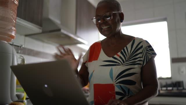 vídeos de stock, filmes e b-roll de mulher idosa fazendo uma videoconferência no laptop em casa - filme imagem em movimento