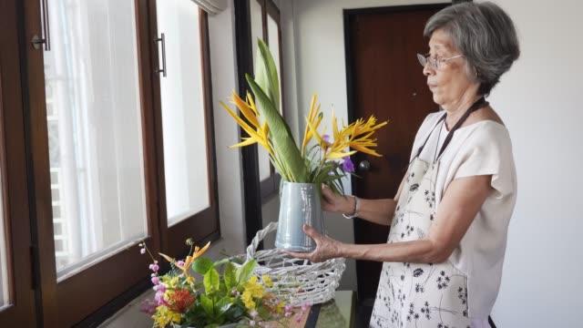 senior woman doing flower arrangement at home - flower arrangement stock videos & royalty-free footage