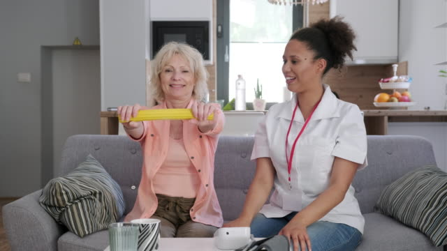 senior woman doing physiotherapy with a healthcare worker at home - nursing assistant stock videos and b-roll footage