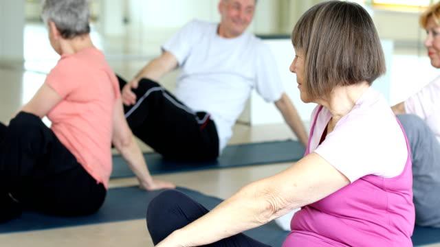 Senior vrouw doen stretching oefening in de klas