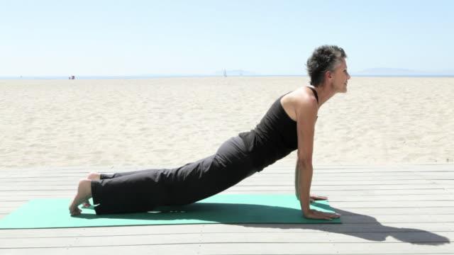 stockvideo's en b-roll-footage met senior woman doing yoga on beach - oefeningen met lichaamsgewicht