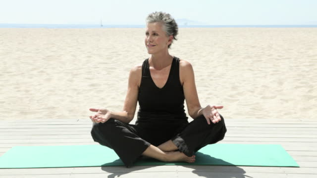 senior woman doing yoga on beach - beautiful people stock videos & royalty-free footage