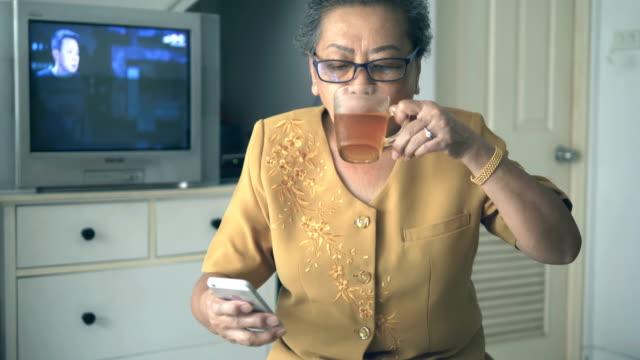 年配の女性の飲酒や携帯電話を使用して - アイスティー点の映像素材/bロール