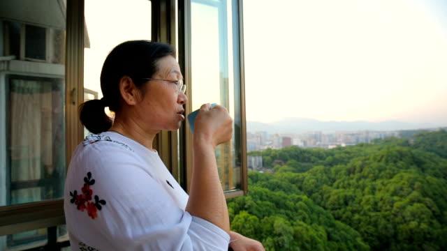 コーヒーを飲んで窓から外を見る年配の女性 - 中国人点の映像素材/bロール
