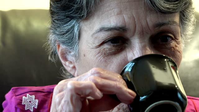 vídeos de stock, filmes e b-roll de sênior mulher bebendo café falando - praça
