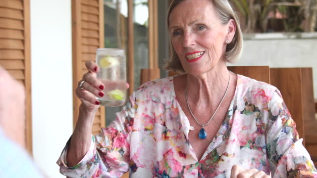 senior woman drinking from glass and toasting with man - floral pattern stock videos & royalty-free footage