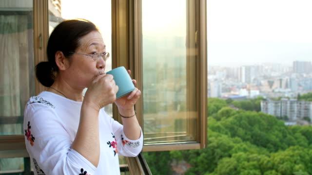 お茶を飲んで窓から外を見る年配の女性 - 中国人点の映像素材/bロール