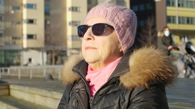 屋外でお茶を飲む先輩女性 - ウィンターコート点の映像素材/bロール