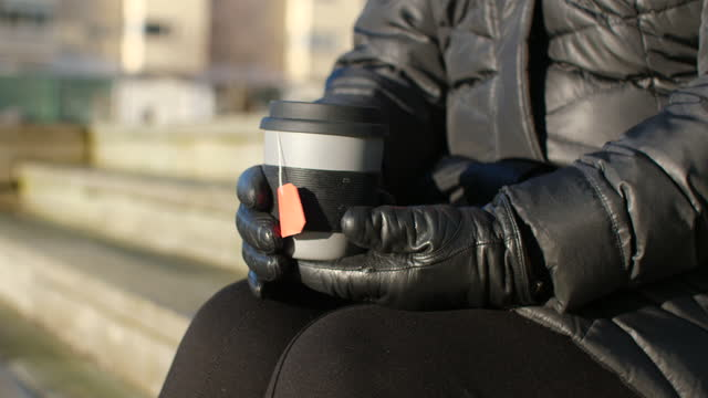 vidéos et rushes de femme aîné buvant le thé à l'extérieur - manteau et blouson d'hiver