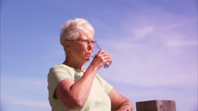 vidéos et rushes de ms senior woman drinking water, overlooking harbor, halifax, nova scotia, canada - eau potable