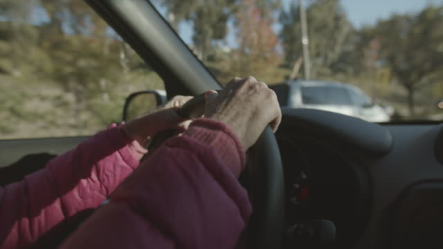 pan ms senior woman driving her car - independence stock videos & royalty-free footage
