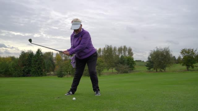 a senior woman driving the ball from the fairway. - sonnenschild stock-videos und b-roll-filmmaterial