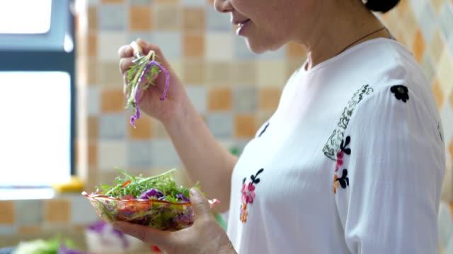 vídeos de stock, filmes e b-roll de mulher sênior que come a salada saudável - vegetable