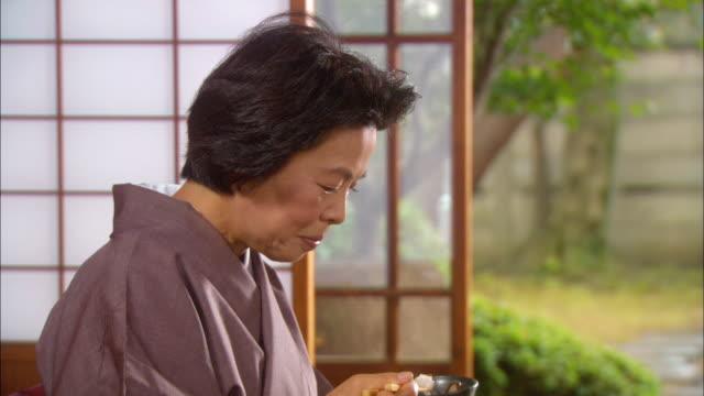 cu tilt up senior woman eating/ tokyo, japan - 食事点の映像素材/bロール