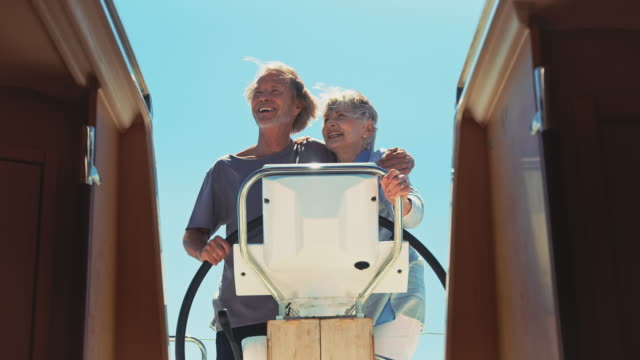 senior woman embracing man driving yacht in summer - yacht stock videos & royalty-free footage