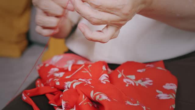 vidéos et rushes de femme aînée brodant cousant ses vêtements de fille tout en s'asseyant dans le salon à la maison. retraité vieille femelle asiatique profiter et sourire sur son passe-temps quand elle a du temps libre. grand-mère porte des cadeaux. - grand mère