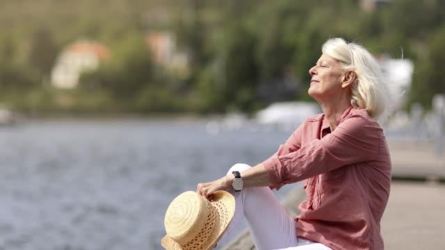 vidéos et rushes de femme aîné appréciant un été au bord de la mer - yeux fermés