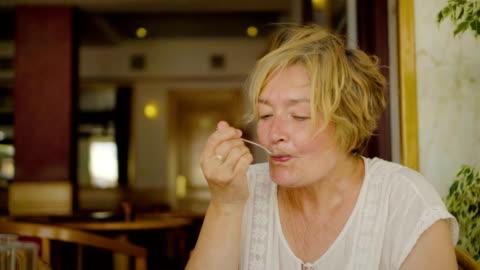 vídeos y material grabado en eventos de stock de mujer mayor disfrutando de pastel - plato de comida