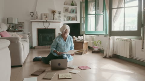 senior woman enjoying coffee and plans for home improvement - grey hair stock videos & royalty-free footage