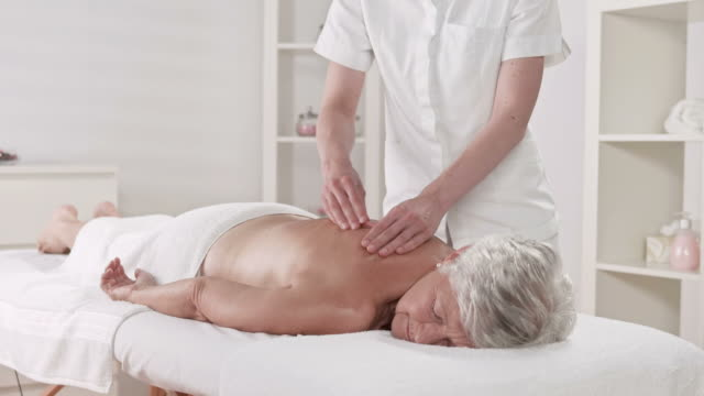 hd dolly: senior woman enjoying professional massage - massage table stock videos and b-roll footage