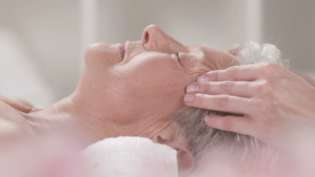 hd dolly: senior woman enjoying relaxing facial massage - beauty spa stock videos & royalty-free footage