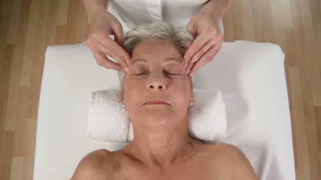 hd crane: senior woman enjoying relaxing facial massage - head massage stock videos and b-roll footage