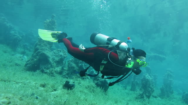 Senior Woman enjoying scuba diving a cenote