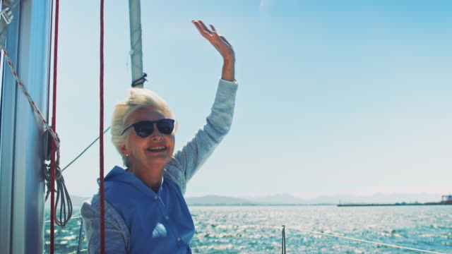 senior woman enjoying while waving in yacht - caucasian ethnicity video stock e b–roll