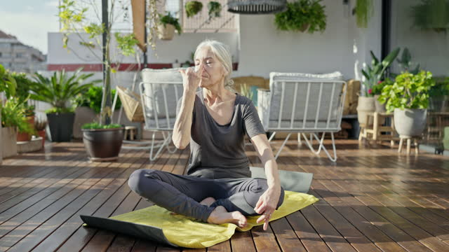 vidéos et rushes de femme aîné appréciant le yoga à l'extérieur sur la plate-forme d'appartement - yeux fermés