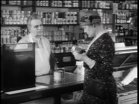 b/w 1933 senior woman examining canned food / male grocer behind counter opening can for woman - can opener stock videos and b-roll footage