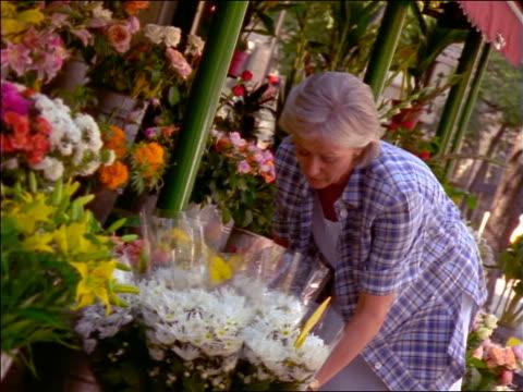 Senior woman examining flowers outside of flower store / France