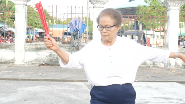 senior woman exercise chinese hand fan dance at car park - hand fan stock videos and b-roll footage