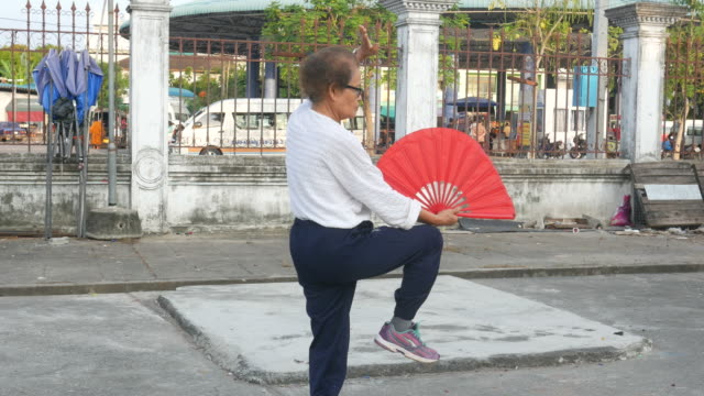 senior woman exercise chinese hand fan dance at car park - overweight yoga stock videos & royalty-free footage