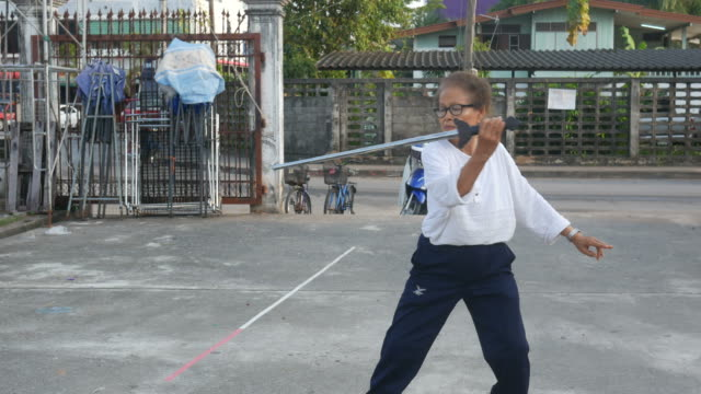 senior woman exercise Chinese sword dance at car park