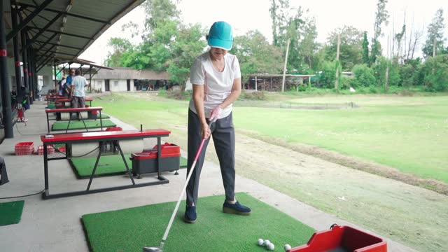 senior woman exercise practicing his golf swing at golf driving range. - senior golf swing stock videos & royalty-free footage