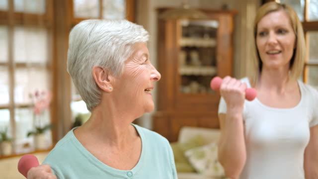 SLO MO Senior woman exercises with nurse supervising her