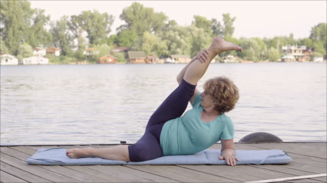 Senior woman exercising beside the river