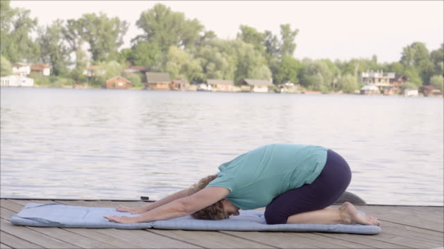 senior woman exercising beside the river - floating moored platform stock videos & royalty-free footage