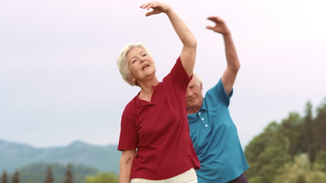 SLO MO Senior woman exercising in the park with her husband