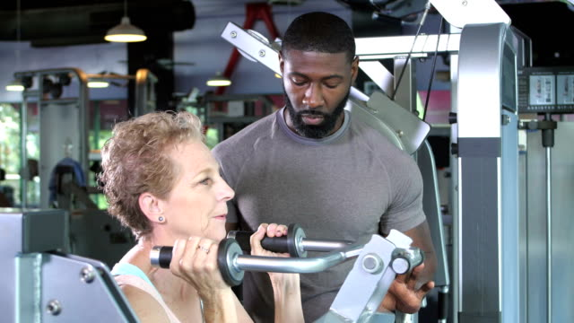 senior woman exercising with personal trainer at gym - instructor stock videos & royalty-free footage