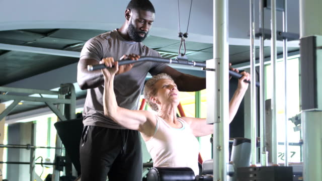 vídeos y material grabado en eventos de stock de senior mujer haciendo ejercicio con entrenador personal en gimnasio - instructor oficio