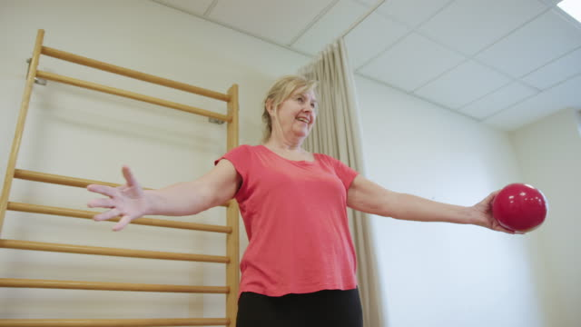 senior woman exercising with sport ball in hospital - rehabilitation center stock videos & royalty-free footage